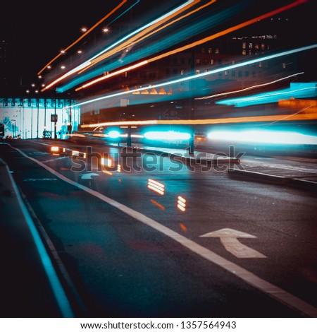 Long exposure light trails in London with red buses in background #1357564943