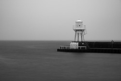 Long exposure lighthouse during heavy fog in black and white. Location is Raa, Helsingborg, Sweden.