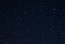 Long exposure night photo of a bright stars. A lot of stars with constellations. Far from the city. Night landscape.