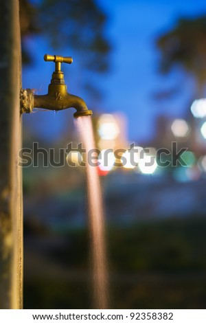 Long exposure night shot of flowing water from old rusty tap in garden or park with city lights in background