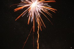 Long exposure of a firework shell exploding with stars visible in background.