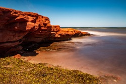 Long exposure of a warm and clear sunny day at Canada's Prince Edward Island red sandstone cliff, next to the Atlantic ocean.