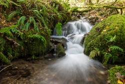 Long exposure of a waterfall flowing into the  river Barle flowing in the Barle Valley at Tarr Steps in Exmoor National Park