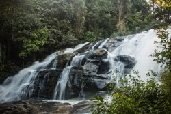 Long exposure of awe-inspiring waterfall surrounded by green vegetation in Mae Klang Luang forest. Chiang Mai, Thailand.