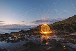 Long exposure of burning steel wool being spun into a sphere on the coastline before sunrise.
