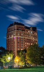 Long exposure of clouds moving across a dark blue sky over a highrise residential building in the Lakeview neighborhood along Lake Shore Drive in Chicago at night.