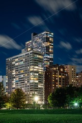 Long exposure of clouds moving across a dark blue sky over modern residential highrise buildings in the Lakeview neighborhood along Lake Shore Drive in Chicago at night.