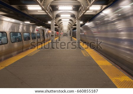 Long Exposure of high speed express train passing station platform waiting departing train at railroad terminal hub. Motion blur right side, stationary on left #660855187