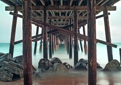 Long exposure of ocean waves crashing on sandy west coast beach on overcast cloudy day underneath symmetrical Balboa Pier in Newport Beach, California near Anaheim
