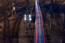 Long exposure of passenger train at railroad station. Railway traffic at nigh, Prague, Czech Republic