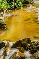 Long exposure of pool of water in small stream with water flowing over large rocks in foreground.