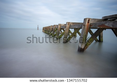 Long exposure of rail jetty into the sea at Landguard Fort Felixstowe in Suffolk.  Still skies and calm water create a relaxing seaside atmosphere.  #1347155702
