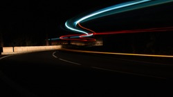 Long exposure of red orange and blue sweeping lights from the traffic on a winding road in the mountains of Tenerife. Showing motion and movement forward in an abstract way with copy space.