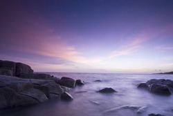 Long exposure of rocky shore over sunset in Thailand