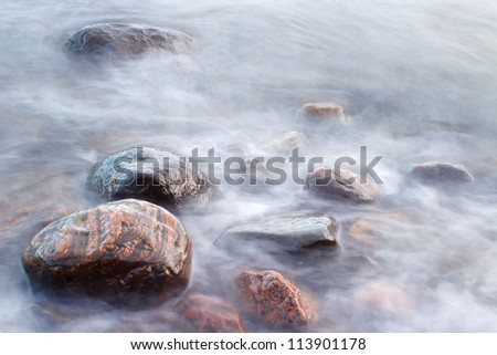 Long exposure of sea waves and beach rocks