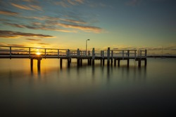 Long exposure of sunrise over pier with milky smooth water.