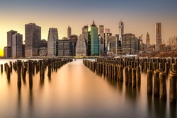 Long exposure of the Lower Manhattan skyline at sunset with an old Brooklyn pier in the foreground
