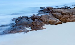 Long exposure of  the sea over rocks and white sand in Thailand