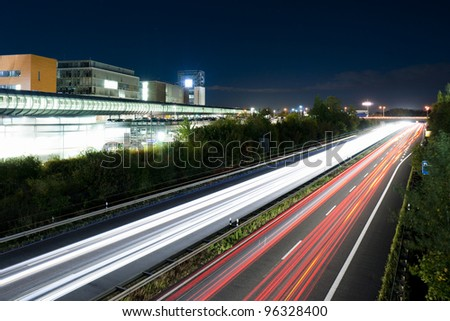 Long exposure of traffic in curve with red and white trails of light. Hanover, Germany.