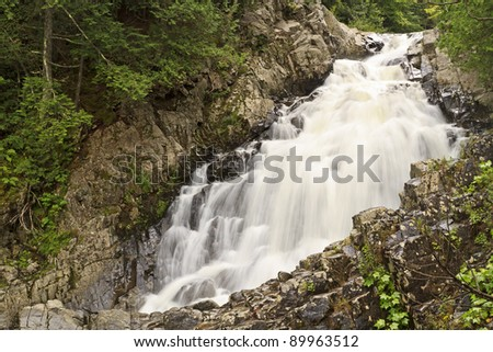Long exposure of water churning through the rocks at Lower Split Rock Falls in the Adirondack Mountains of New York - stock photo
