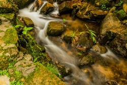 Long exposure of water in small stream flowing rapidly through large stones and rocks.