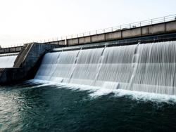 Long exposure panorama of white water flowing down water reservoir lake dam sustainability renewable green hydro power plant Rhein Rhine river Switzerland Germany Europe