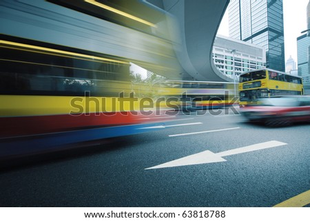 Long exposure photo of bus moving on urban road. Motion blur over city background. Cross processed colors.