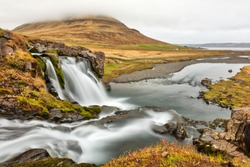 Long exposure photo of Kirkjufellsfoss facing Kirkjufell (