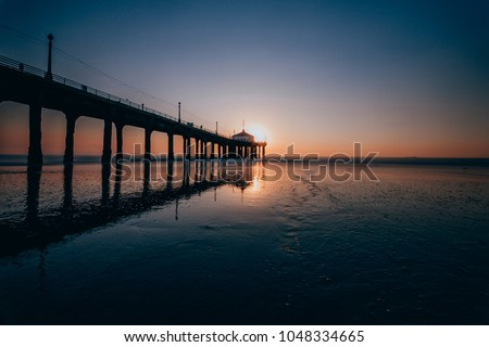 Long Exposure photo of Manhattan Beach Pier from the side with the reflective wet sand during sunset in Manhattan Beach, California #1048334665