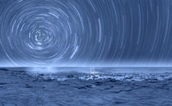 Long exposure photo of night sky star trail over the frozen sea - Tromso, Norway