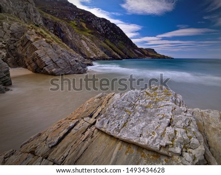 Long exposure photo of the incoming tide between the rocks at Maghera Beach, Co. Donegal with huge sea cliffs in the background #1493434628