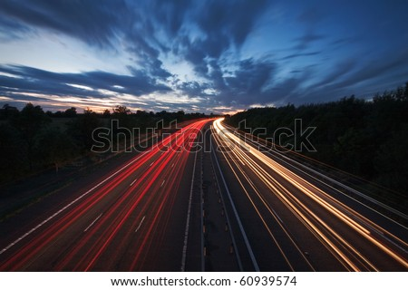 Long exposure photo of traffic on the move at dusk on the M40 motorway in England.