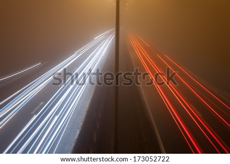 Long exposure photo on a highway with car light trails at misty night