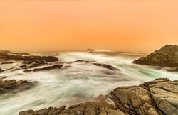 Long exposure photo, silk effect in water. The sea cliffs are filled with foam, which forms a fog, orange sky. Coastal landscape