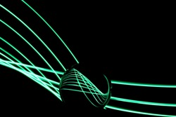 Long exposure photograph of neon colour in an abstract swirl, parallel lines pattern against a black background with reflections in a glass orb. Light painting photography.