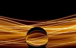 Long exposure photograph of neon gold colour in an abstract swirl, parallel lines pattern against a black background with reflections in a glass orb. Light painting photography.