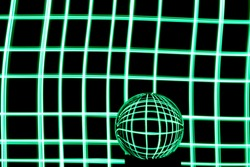 Long exposure photograph of neon green colour in a checkered crisscross parallel lines pattern against a black background with reflections in a glass orb. Light painting photography.