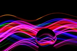 Long exposure photograph of neon multi colour in an abstract swirl, parallel lines pattern against a black background with reflections in a glass orb. Light painting photography.