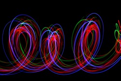 Long exposure photograph of neon multi colour in an abstract swirly loops lines pattern against a black background. Light painting photography.