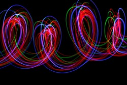 Long exposure photograph of neon multi colour loops in an abstract swirls pattern against a black background. Light painting photography.