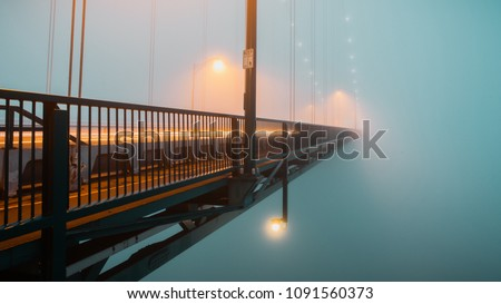 Long exposure photograph of traffic passing along a suspension bridge disappearing into the fog