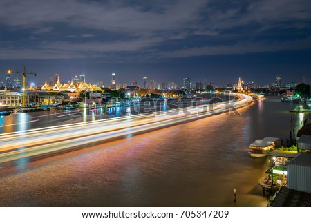Long exposure photography at night on Chao Phraya River and riverside view created highlight shadow and movement of boat, ship, cloud.