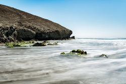 Long exposure photography. The waves of the sea leave trails of white foam on the rocks covered with green algae.