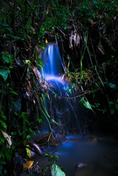 long exposure picture of little waterfall with glowing blue water.