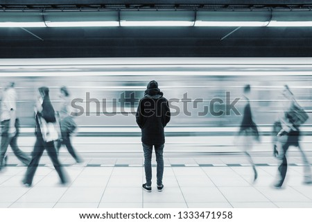 Long exposure picture with lonely young man shot from behind at subway station with blurry moving train and walking people in background