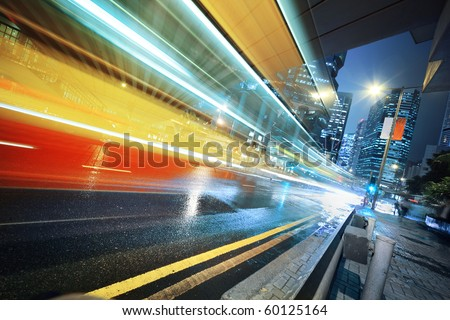 Long exposure shot of blurred bus speeding through night street.