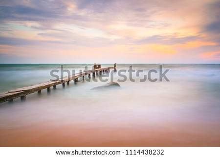 Long exposure shot of the ocean and a pier in a sunset on Phu Quoc island in Vietnam.