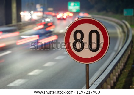 Long exposure shot of traffic sign showing 80 km/h speed limit on a highway full of cars in motion blur during the night #1197217900