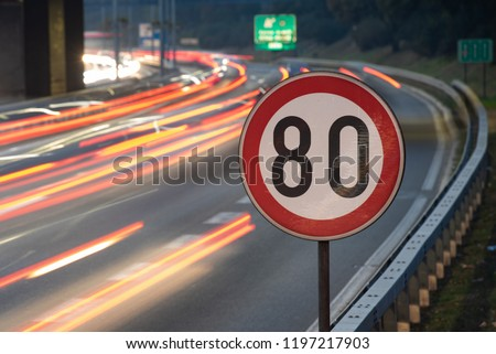 Long exposure shot of traffic sign showing 80 km/h speed limit on a highway full of cars in motion blur during the night #1197217903