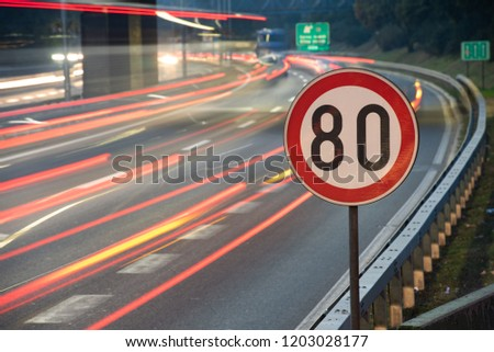Long exposure shot of traffic sign showing 80 km/h speed limit on a highway full of cars in motion blur during the night #1203028177